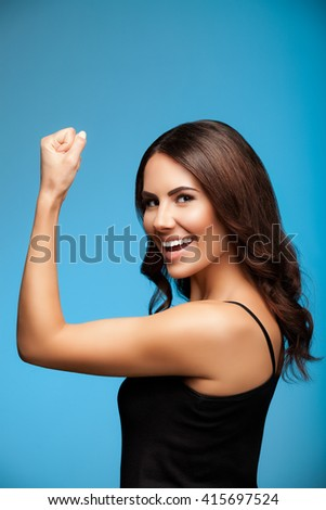 Portrait of cheerful smiling young woman happy gesturing, over blue background - stock photo