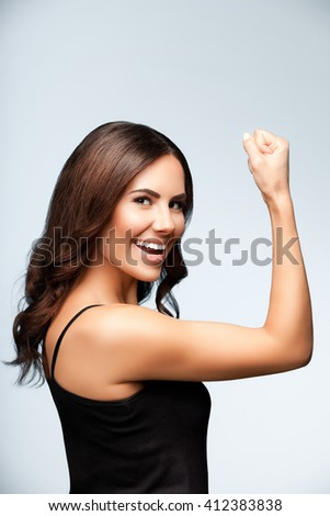Portrait of cheerful smiling young woman happy gesturing, over bright grey background - stock photo