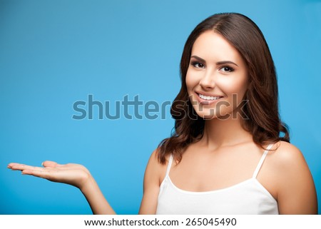 Portrait of cheerful smiling young woman in white casual clothing showing copyspace or something, over blue background - stock photo