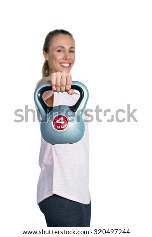 Portrait of cheerful sporty woman exercising with kettlebell against white background - stock photo