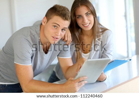 Portrait of cheerful students connected on digital tablet - stock photo