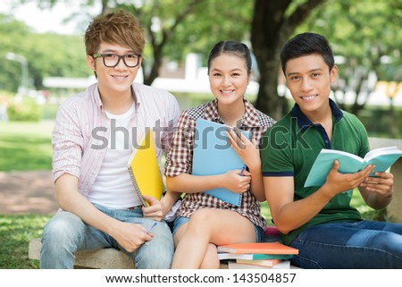 Portrait of cheerful students sitting with notebooks and looking at camera