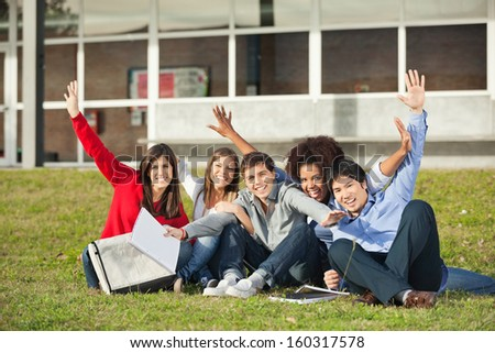 Portrait of cheerful students with hands raised sitting on grass at university campus - stock photo