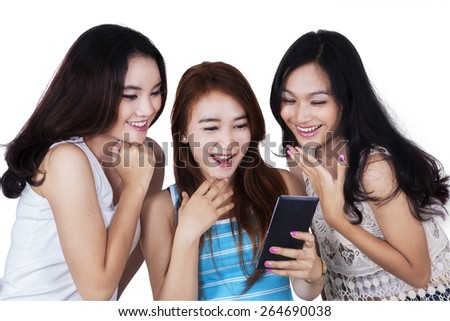 Portrait of cheerful teenage girls looks happy when reading a message together on mobile phone - stock photo