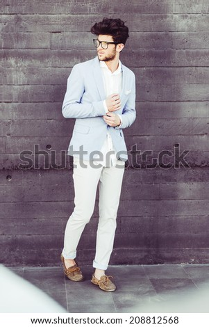 Portrait of cheerful trendy guy with black eyeglasses on wearing blue blazer jacket - stock photo