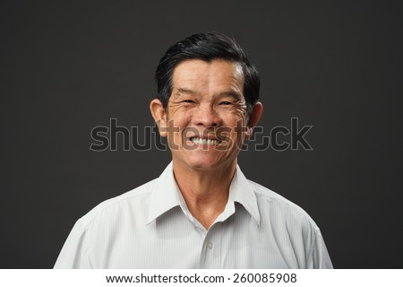 Portrait of cheerful Vietnamese old man - stock photo