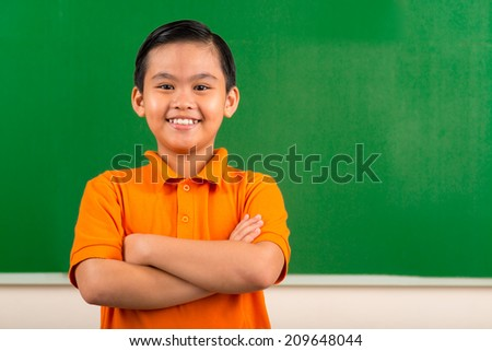 Portrait of cheerful Vietnamese schoolboy with his arms crossed - stock photo