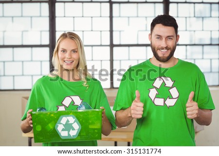 Portrait of cheerful volunteers in recycling symbol tshirts at office