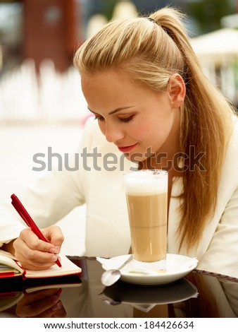 Portrait of cheerful white collar woman writing notes during her lunch - stock photo