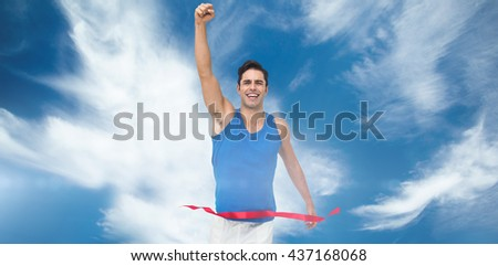 Portrait of cheerful winner athlete crossing finish line against blue sky with clouds - stock photo
