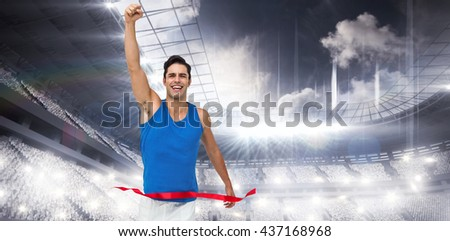 Portrait of cheerful winner athlete crossing finish line against sports arena - stock photo