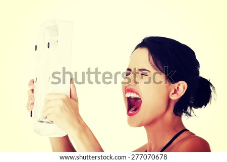 Portrait of cheerful woman holding a scale. - stock photo