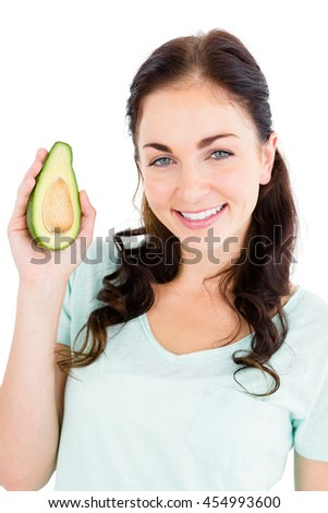 Portrait of cheerful woman holding avocado against white background - stock photo