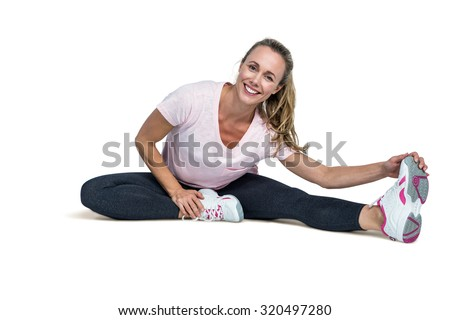 Portrait of cheerful woman touching toes while exercising over white background - stock photo