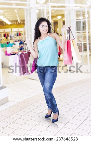 Portrait of cheerful woman with curly hair standing in the mall while holding shopping bags - stock photo