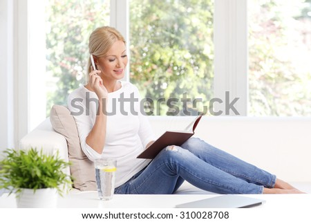 Portrait of cheerful woman working at home and making call while making appointment.