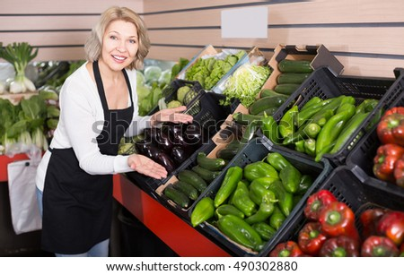 Portrait of cheerful woman working in grocery and smiling