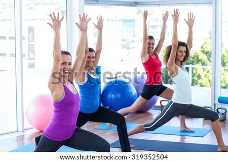 Portrait of cheerful women doing low warrior pose in fitness studio on exercise mat - stock photo