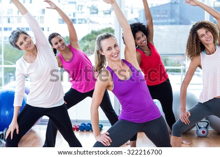 Portrait of cheerful women exercising with arms raised in fitness studio - stock photo