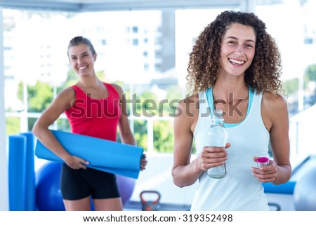 Portrait of cheerful women in fitness studio holding exercise mat and water bottle - stock photo