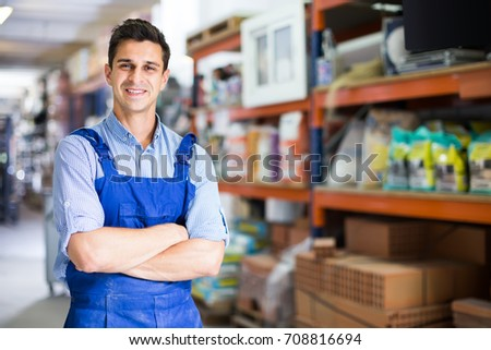 Portrait of cheerful working man in uniform on his workplace in building store.