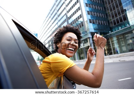 Portrait of cheerful young african woman looking out the car window with her arms raised - stock photo