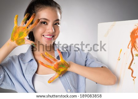 Portrait of cheerful young artist with hands in paints - stock photo