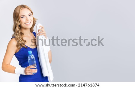 Portrait of cheerful young attractive blond woman in fitness wear with bottle of water and towel, with copyspace, over grey background - stock photo