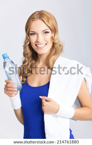 Portrait of cheerful young attractive blond woman in fitness wear with bottle of water and towel, over grey background - stock photo