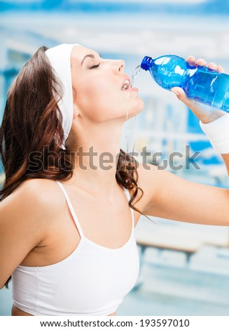 Portrait of cheerful young attractive woman  drinking water, at fitness club or gym - stock photo