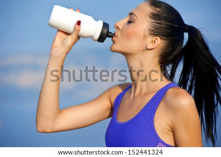 Portrait of cheerful young attractive woman drinking water, outdoors  - stock photo