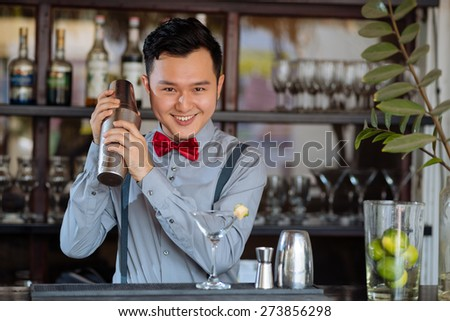 Portrait of cheerful young bartender shaking a cocktail - stock photo