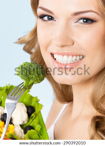 Portrait of cheerful young beautiful blond woman with healthy vegetarian salad with broccoli, against blue background. Healthy eating and dieting concept. - stock photo