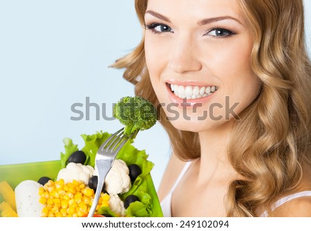 Portrait of cheerful young beautiful woman with healthy vegetarian salad with broccoli, against blue background. Healthy eating and dieting concept. - stock photo