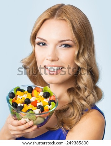 Portrait of cheerful young beautiful woman with vegetarian salad, against blue background. Healthy eating and diet concept. - stock photo