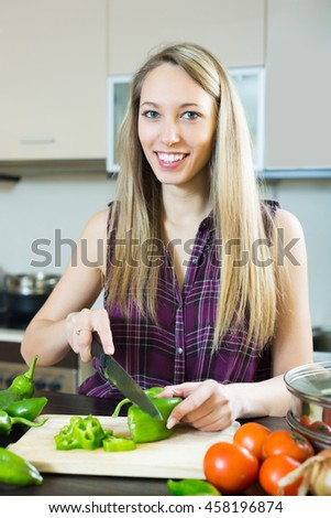 Portrait of cheerful young blonde woman cooking with vegetables at kitchen