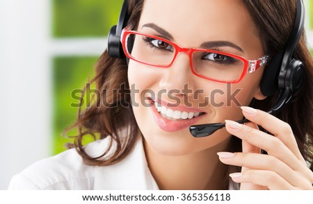 Portrait of cheerful young brunette businesswomen, support phone female operator or call center worker, in headset and glasses. Help and consulting concept.  - stock photo