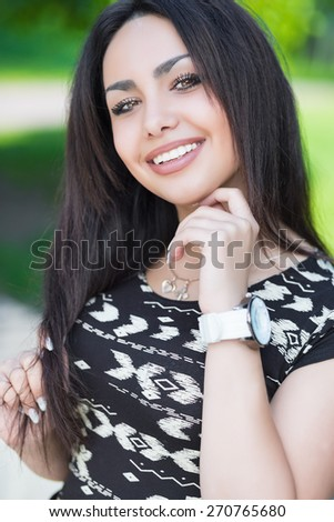 Portrait of cheerful young brunette posing outdoors - stock photo