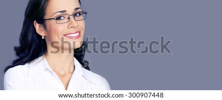Portrait of cheerful young businesswoman in glasses, with blank copyspace area for text or slogan, posing at studio, over violet background - stock photo