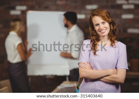 Portrait of cheerful young businesswoman with arms crossed standing in office
