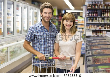 Portrait of cheerful young couple in supermarket. Looking camera - stock photo