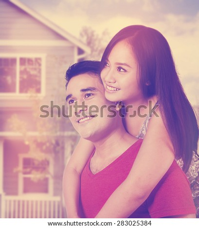 Portrait of cheerful young couple standing near new house, shot with instagram filter - stock photo