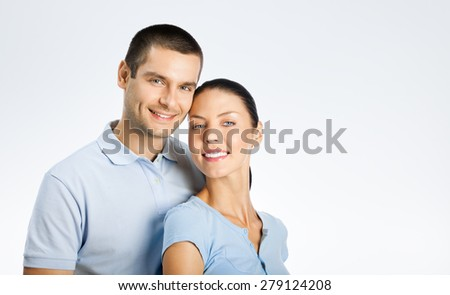 Portrait of cheerful young couple, with copyspace blank area for text or slogan, over grey background - stock photo