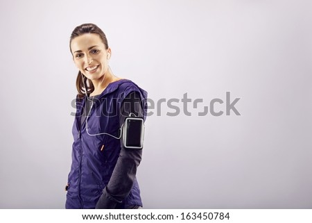 Portrait of cheerful young female runner listening to music while standing against grey background. Caucasian fitness woman in sportswear smiling. - stock photo