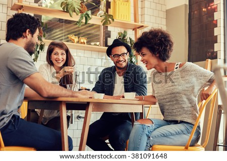 Portrait of cheerful young friends having fun while talking in a cafe. Group of young people meeting in a cafe. - stock photo