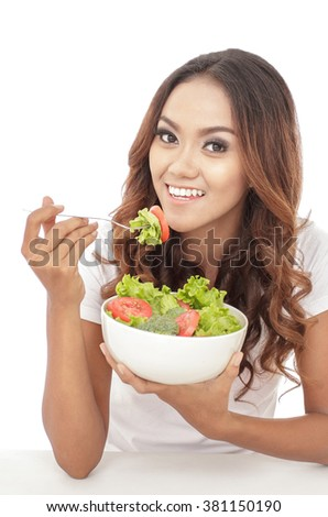 portrait of cheerful young girl eating vegetables salad isolated on white background