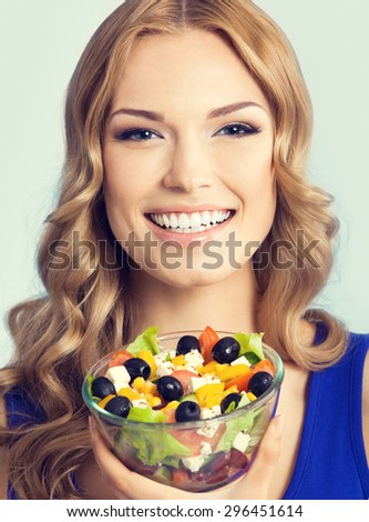 Portrait of cheerful young lovely woman with vegetarian salad, against blue background. Healthy eating and diet concept. - stock photo