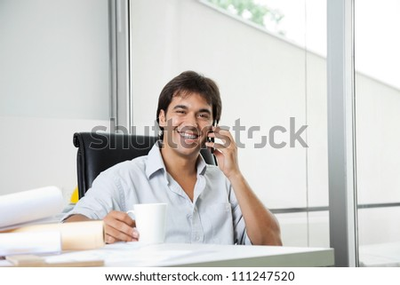 Portrait of cheerful young male architect answering phone call while having coffee - stock photo