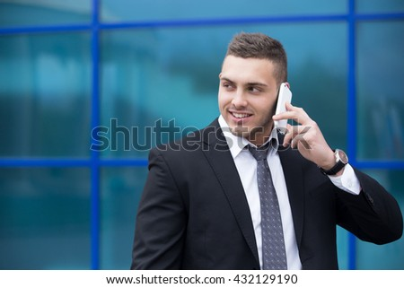 Portrait of cheerful young man looking sideways while talking on smartphone outdoors. Happy handsome caucasian man using mobile phone, making call on the street in summer. Copy space - stock photo
