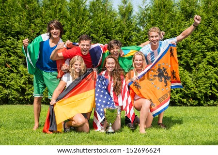 Portrait of cheerful young multiethnic athletes with various national flags celebrating in park - stock photo